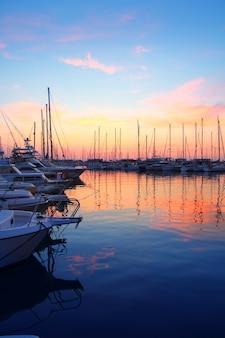 Barca di sport di tramonto di alba del porticciolo variopinta