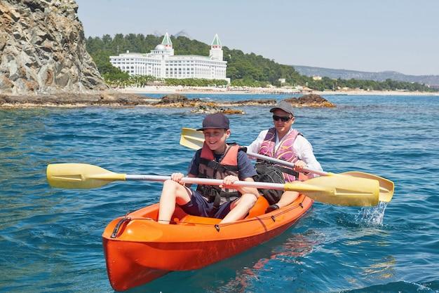 Barca in kayak vicino a scogliere in una giornata di sole. kayak in una baia tranquilla. viste incredibili. viaggi, concetto di sport. stile di vita. una famiglia felice.