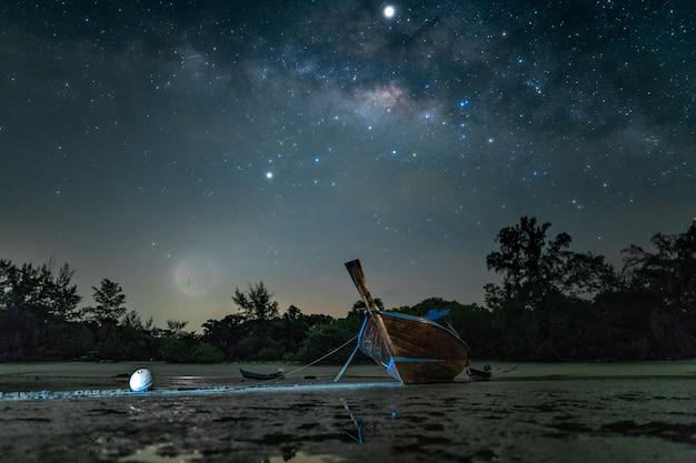 Barca in legno sulla spiaggia di notte