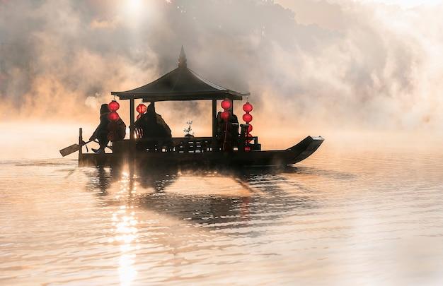Barca in stile cinese nel lago con la luce del mattino e la nebbia.