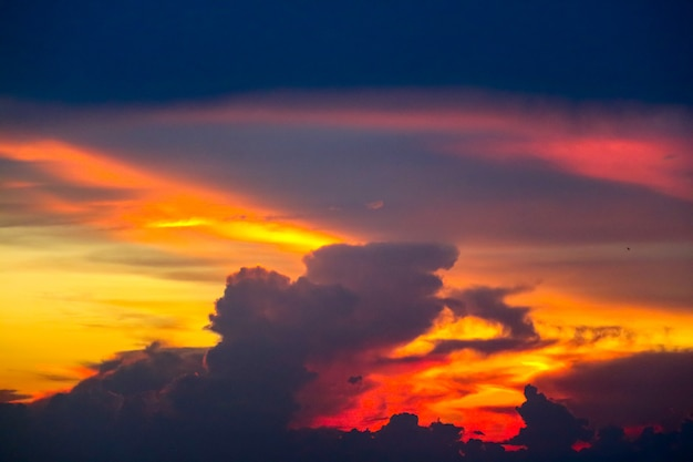 Barca multicolore di tramonto della nuvola di fiamma sul mare e sul cielo