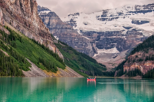 Barca rossa nel lago vicino alla montagna