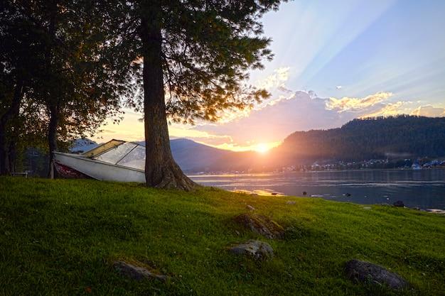 Barca sul lago a priorità bassa del giorno di estate al tramonto