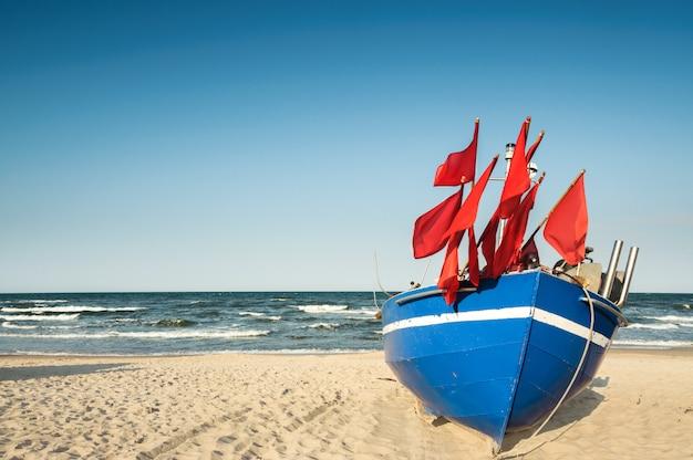 Barca tedesca tradizionale del pescatore su una riva sabbiosa