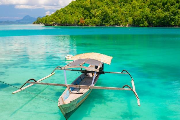 Barca tradizionale che galleggia sulla laguna modificata blu trasparente delle isole togean a distanza, indonesia.