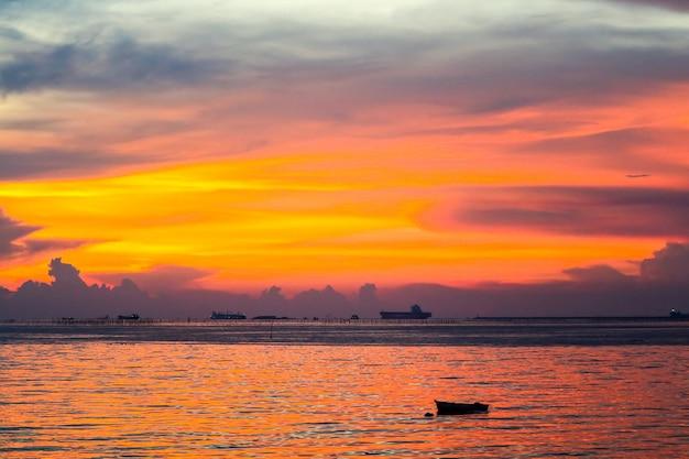 Barca variopinta di tramonto della nuvola di fiamma sul mare e sul cielo