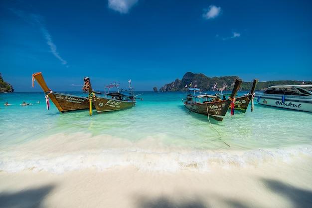 Barche a coda lunga che parcheggiano al bianco e alla spiaggia sull'isola di phi di phi in tailandia