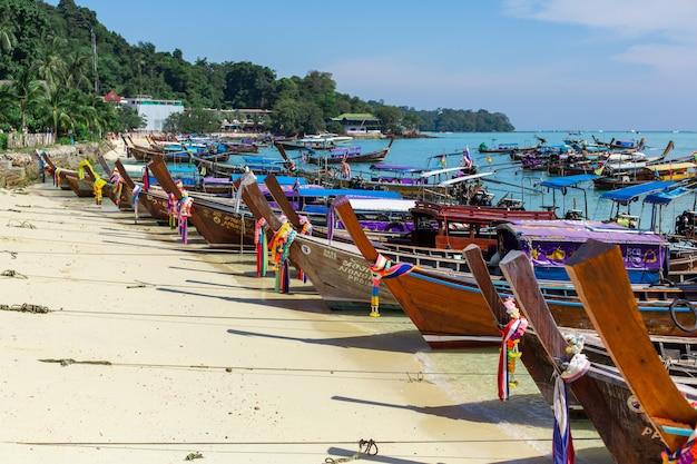 Barche di legno tradizionali di pesca tailandese avvolte con nastri colorati.