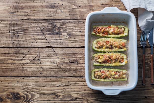 Barche di zucchine ripiene al forno con funghi di pollo tritati e verdure con formaggio su una teglia. vista dall'alto copyspace