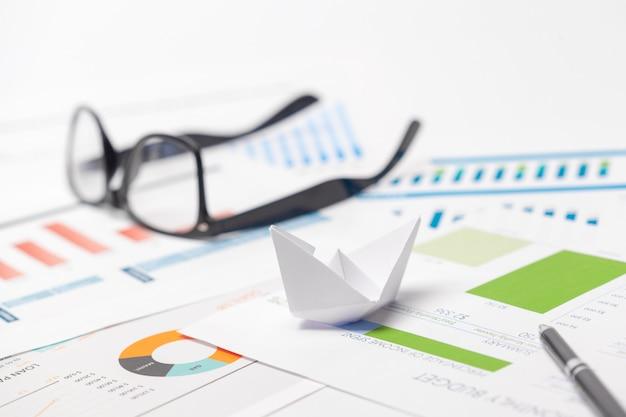 Barche fatte di grafico di carta su notebook con occhiali e penna