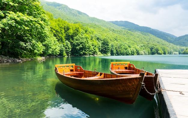 Barche in legno al molo sul lago di montagna