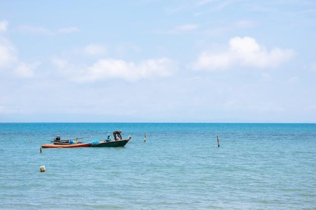 Barche locali del pescatore dalla parte di sinistra che galleggia sopra il mare con il cielo luminoso nella priorità bassa
