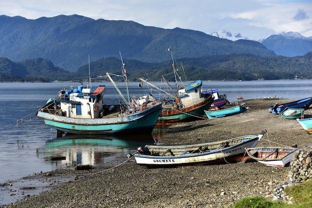 Barche parcheggiate in riva al lago con le montagne