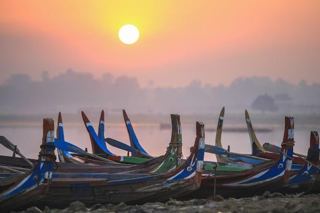 Barche variopinte sulla riva con alba vicino al ponte di u bein, lago taungthaman vicino ad amarapura, myanmar