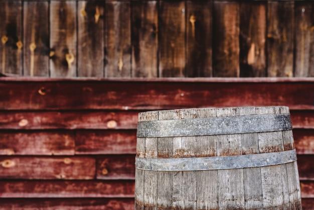 Barile di legno, dietro il fondo di tavole di legno invecchiate, per conservare bevande alcoliche come vino o whisky