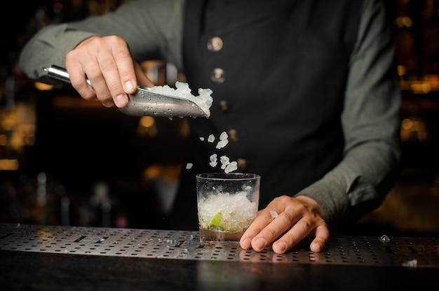 Barista aggiungendo cubetti di ghiaccio nel bicchiere da cocktail. processo di preparazione del cocktail caipirinha
