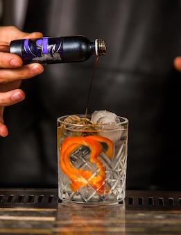 Barista aggiungendo una bevanda alcolica in un bicchiere con cocco, arancia sbucciata e cubetti di ghiaccio