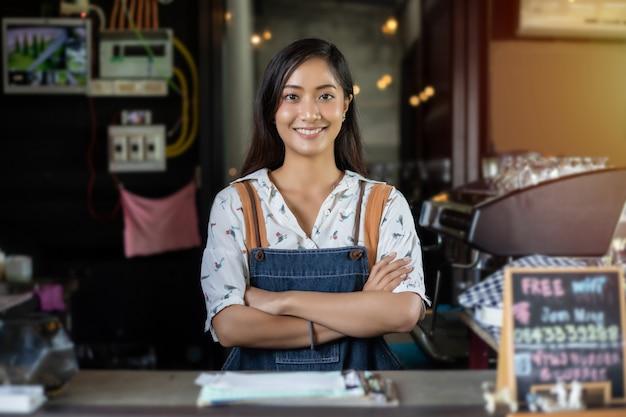 Barista asiatico delle donne che sorride e che utilizza la macchina del caffè nel contatore della caffetteria - concetto del caffè dell'alimento e della bevanda del piccolo imprenditore della donna lavoratrice