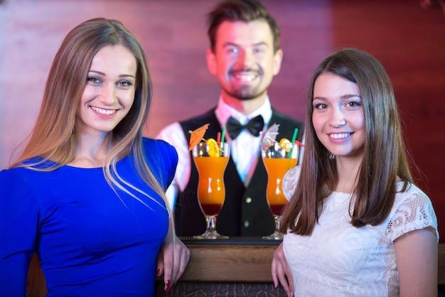 Barista bello che serve cocktail alla donna attraente.