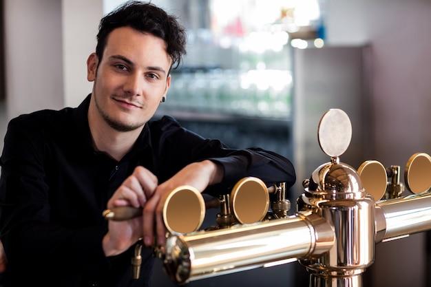 Barista bello che si appoggia sul rubinetto della birra