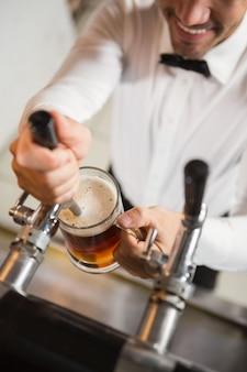 Barista bello che versa una pinta di birra