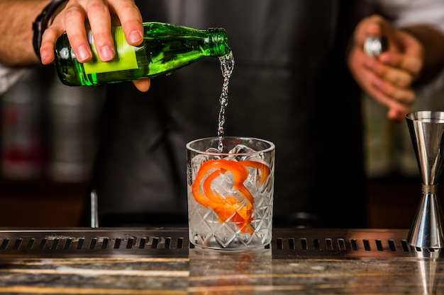 Barista che aggiunge gin tonic nel bicchiere con cubetti di ghiaccio e buccia d'arancia sbucciata