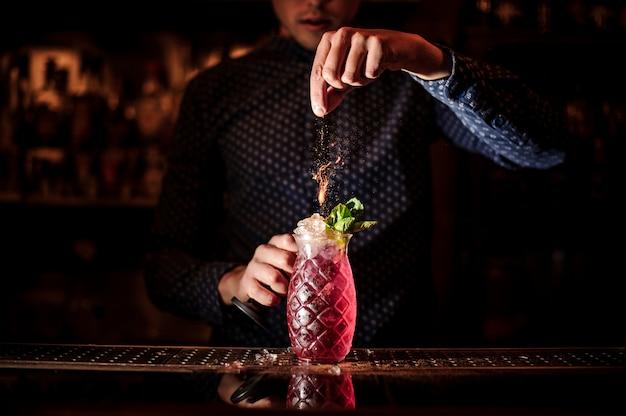 Barista che aggiunge le spezie al cocktail estivo fresco e dolce di mojito alla fragola