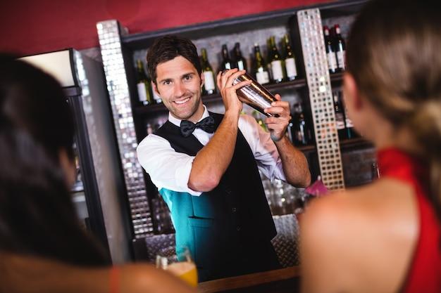 Barista che agita cocktail in agitatore al bancone del bar