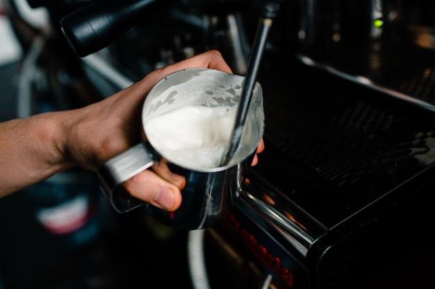 Barista che batte la schiuma di latte con la macchina