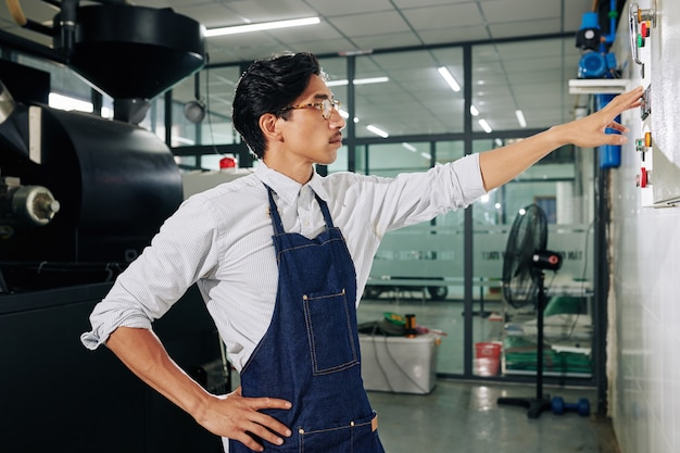 Barista che controlla il processo di tostatura del caffè