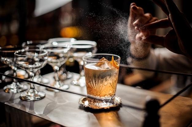 Barista che decora cocktail estivo fresco vecchio stile con ghiaccio e scorza d'arancia