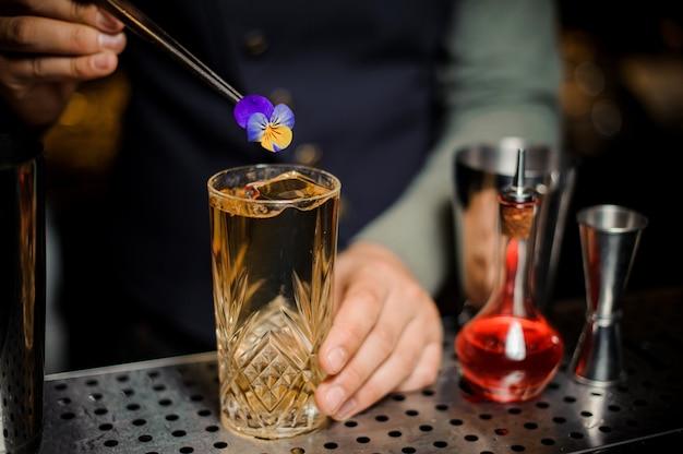 Barista che decora un dolce cocktail alcolico con un fiore