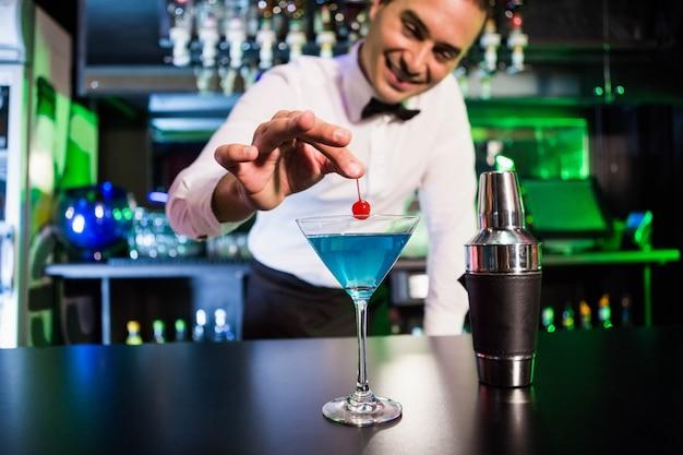 Barista che guarnisce cocktail con la ciliegia sul bancone del bar nel bar