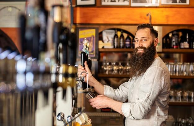 Barista che lavora felicemente nel suo bar.