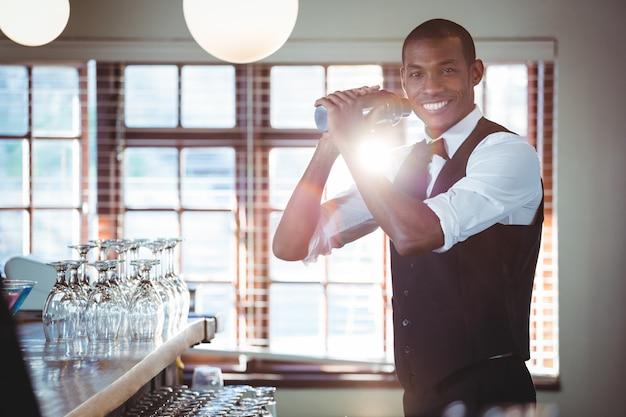 Barista che mescola una bevanda del cocktail nello shaker
