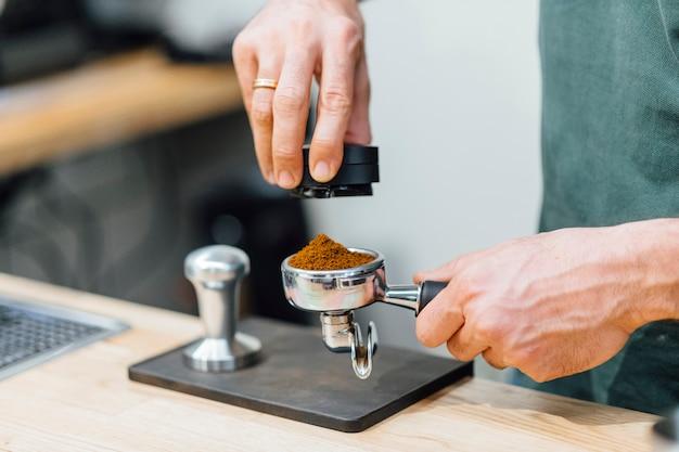 Barista che preme il caffè al portafiltro