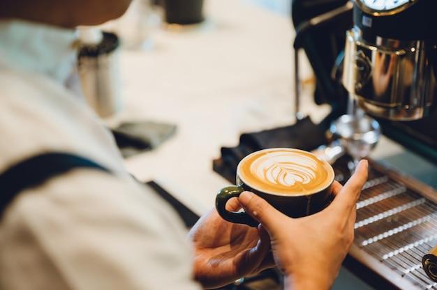 Barista che produce latte art, fuoco sparato in tazza di latte e caffè