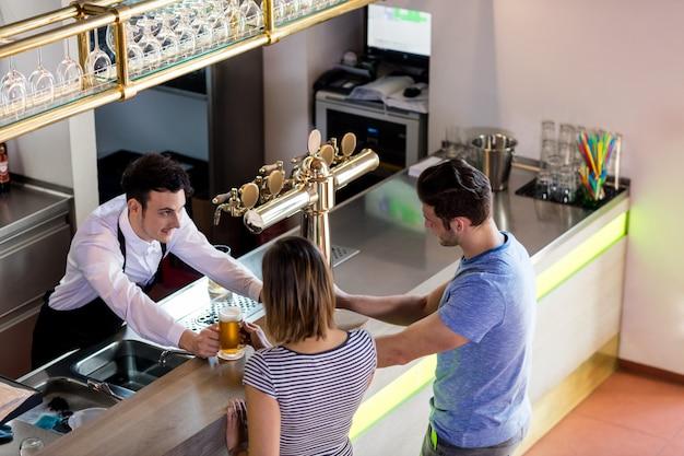 Barista che serve birra per coppia