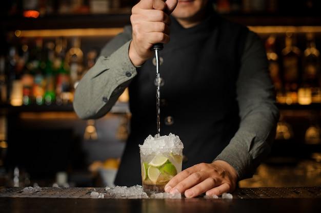 Barista che versa cachaca nel bicchiere da cocktail. processo di preparazione del cocktail caipirinha