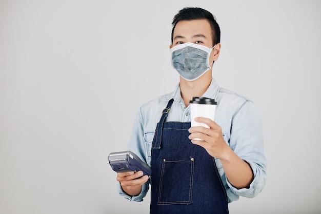 Barista con caffè e terminale di pagamento