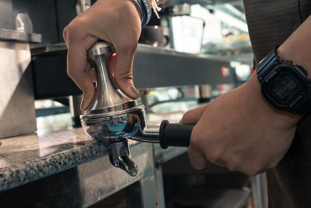 Barista con portafiltro e manomissione del caffè mentre prepara un caffè espresso