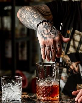 Barista con tatuaggi che prepara un cocktail rosso con whisky.