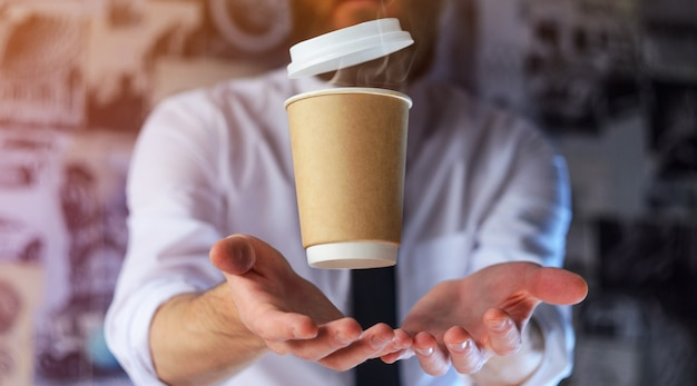 Barista e levitante tazza di carta di caffè caldo