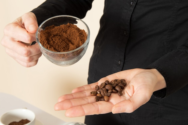 Barista femmina in pantaloni camicia nera con caffè marrone essiccato ingredienti attrezzature tè sul muro bianco