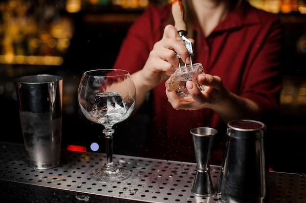 Barista femminile che prepara il cubetto di ghiaccio per produrre cocktail