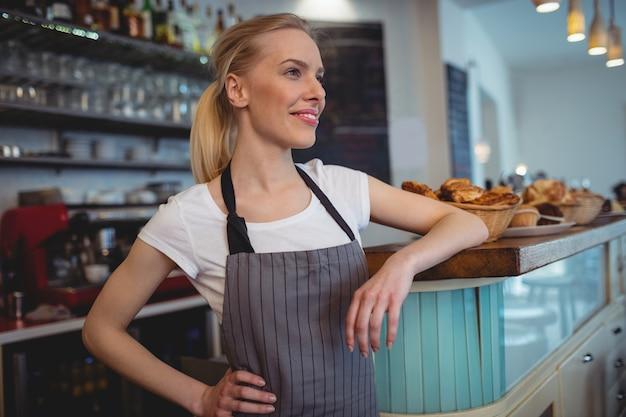 Barista femminile felice che sta al contatore in caffetteria