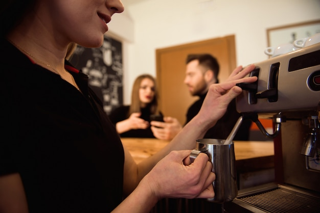 Barista femminile professionale che tiene la brocca di metallo che scalda latte usando la macchina del caffè.