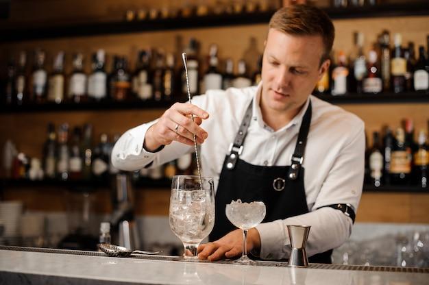 Barista giovane rossa mescolando bevanda alcolica con cubetti di ghiaccio