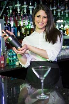Barista grazioso che mescola una bevanda del cocktail nell'agitatore di cocktail alla barra