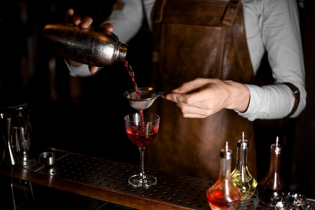 Barista in grembiule di cuoio che versa una bevanda alcolica rossa dall'agitatore d'acciaio attraverso il setaccio
